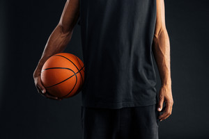 Cropped image of an african basketball player holding ball isolated on a black background