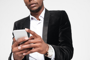 Cropped image of attractive african businessman chatting by his phone. Isolated over white background.
