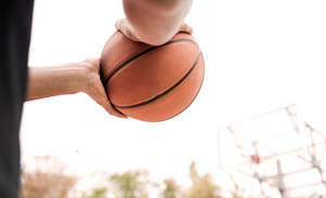 Cropped image of basketball player's hands with ball