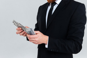 Cropped image of business man in black suit holding and recounts money. Isolated gray background