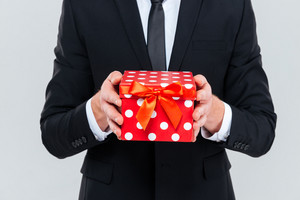 Cropped image of business man in black suit holding gift in hands. Isolated gray background