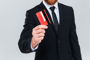 Cropped image of business man in suit holding credit card in hand. Isolated gray background
