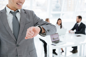 Cropped image of business man looking at wristwatch with colleagues on background in office