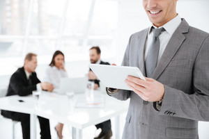 Cropped image of Business man using tablet computer in office with colleagues by the table on background