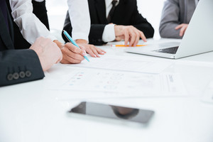 Cropped image of business team by the table with laptop and documents