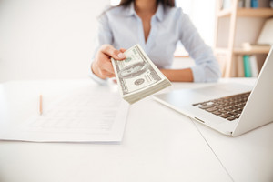 Cropped image of businesswoman dressed in white shirt sitting in her office and give money to camera
