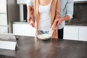 Cropped image of couple in kitchen with tablet. on the table