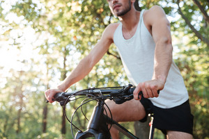 Cropped image of cyclist in forest. man in singlet. side view
