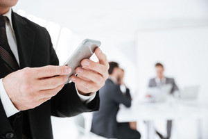 Cropped image of Elderly Business man holding phone in office with colleagues on background