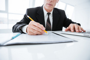 Cropped image of Elderly business man sitting by the table and writing something in documents