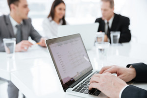 Cropped image of Elderly business man sitting by the table with business partners and using laptop