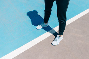 Cropped image of female legs in sneakers and black pants standing on a blue sports field, close-up