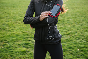 Cropped image of female runner in warm clothes in autumn park using her phone