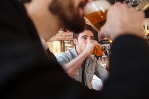 Cropped image of friends drinking beer on bar in cafe