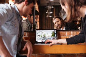 Cropped image of friends sitting in bar near the mirror and looking at laptop. Back view