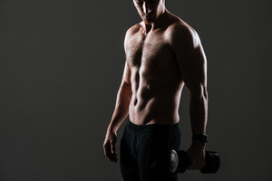Cropped image of handsome sportsman standing with dumbbell in gym over grey background.