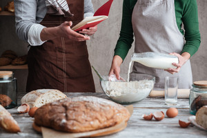 Cropped image of loving couple bakers standing near bread and cooking. Man holding notebook.
