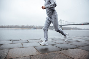 Cropped image of man in gray sportswear running near the water. Side view
