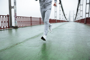 Cropped image of Man in gray sportswear running on bridge