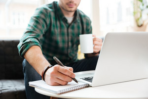 Cropped image of man in green shirt sitting at the table with laptop, holding cup of tea and writing something on notebook
