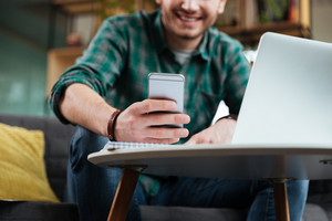 Cropped image of man in green shirt sitting on sofa by the table with laptop and writing message on phone in office. Focus on phone. Coworking