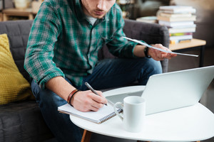 Cropped image of man in green shirt sitting on sofa with laptop and documents and writing by the table. Coworking