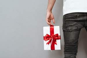 Cropped image of man with gift. Back view. Isolated gray background