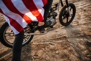 Cropped image of men leg starting his motorcycle in desert