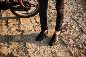 Cropped image of men legs standing near motorbike at the desert