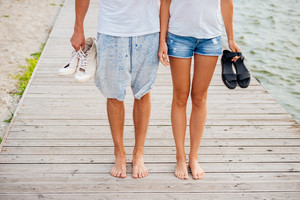 Cropped image of romantic young beautiful couple walking on the beach holding hands