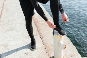 Cropped image of runner near the sea. man preparing. tying shoelaces