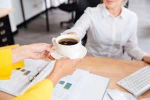 Cropped image of secretary bringing cup of coffee for her boss in office