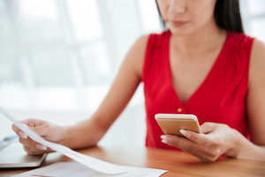 Cropped image of Serious woman in red shirt sitting by the table with phone and documents in office. Focus on phone
