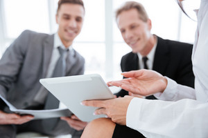 Cropped image of three business people with tablet computer. Smiling business men. Focus on tablet