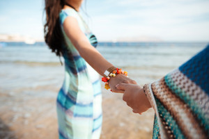Cropped image of two girls holding hands on the beach