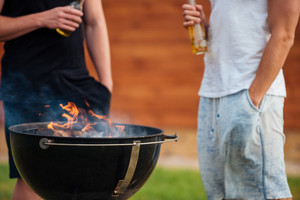 Cropped image of two men holding a beer bottle while preparing barbecue grill in park zone
