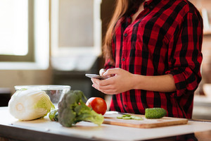 Cropped image of woman in red shirt standing at the table and writing message on phone in kitchen. Side view