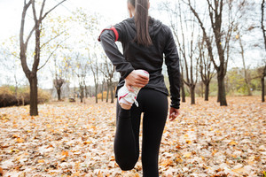 Cropped image of woman runner in warm clothes make sport exercise in autumn park