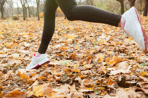 Cropped image of woman runner in warm clothes running in autumn park