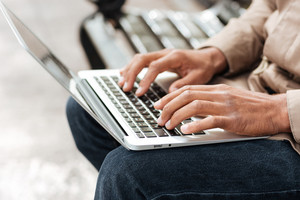 Cropped image of young african man with laptop sitting on a wooden bench and typing.