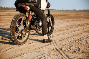 Cropped image of young brutal man in a black jacket and glasses driving retro motorcycle