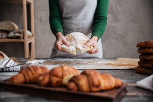 Cropped image of young lady baker standing near croissants holding bread