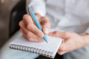Cropped image of young man dressed in white shirt writing notes in notebook. Coworking.