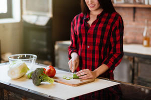 Cropped image of young woman in red shirt cooking in kitchen. Standing at the table. Side view
