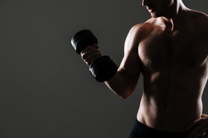 Cropped photo of attractive athlete standing with dumbbell in gym over grey background.