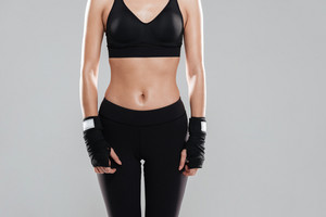 Cropped photo of attractive young fitness lady posing over grey background.