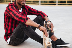 Cropped photo of dark skinned young man sitting near his skateboard. Against nature background.