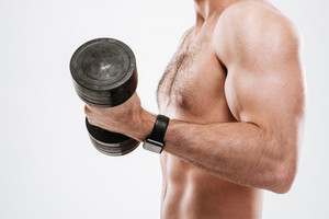 Cropped photo of handsome athlete standing with dumbbell in gym over white background.