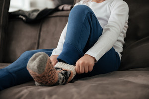 Cropped photo of pretty little boy puts on socks while sitting on sofa at home.