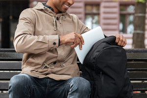 Cropped photo of young cheerful african man getting laptop from the backpack.